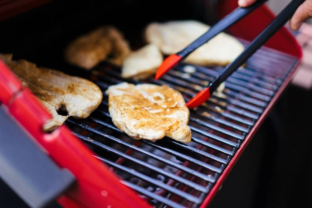 Chicken breasts being grilled on an open flame with a red barbeque grill and matching kitchen tongs.