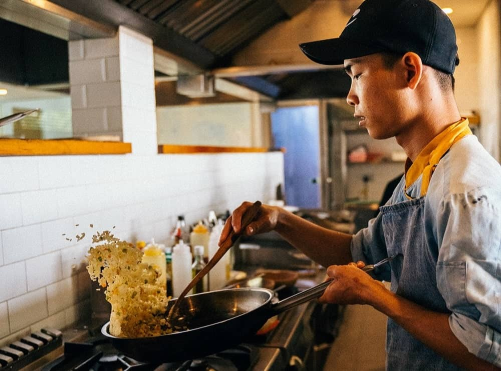 Asian man cooking fried rice on the pan.
