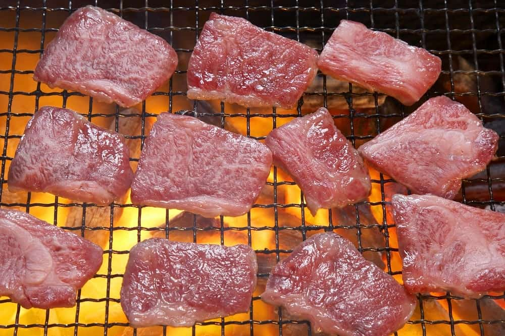 This is a close look at a batch of meat grilling.