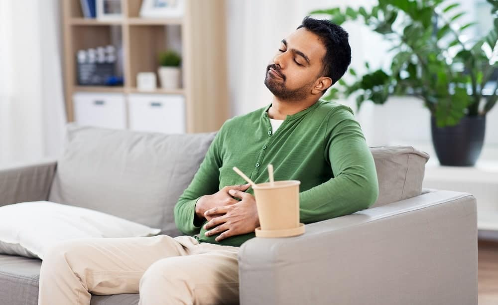 A man sitting and feeling full after eating a lot.