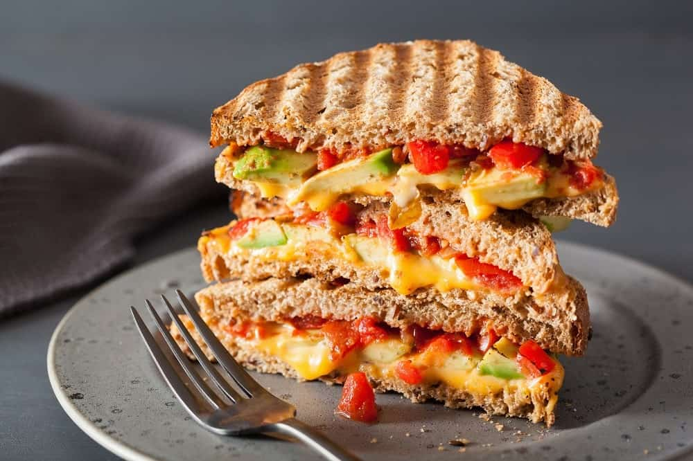 This is a grilled cheese sandwich with avocado and tomatoes.