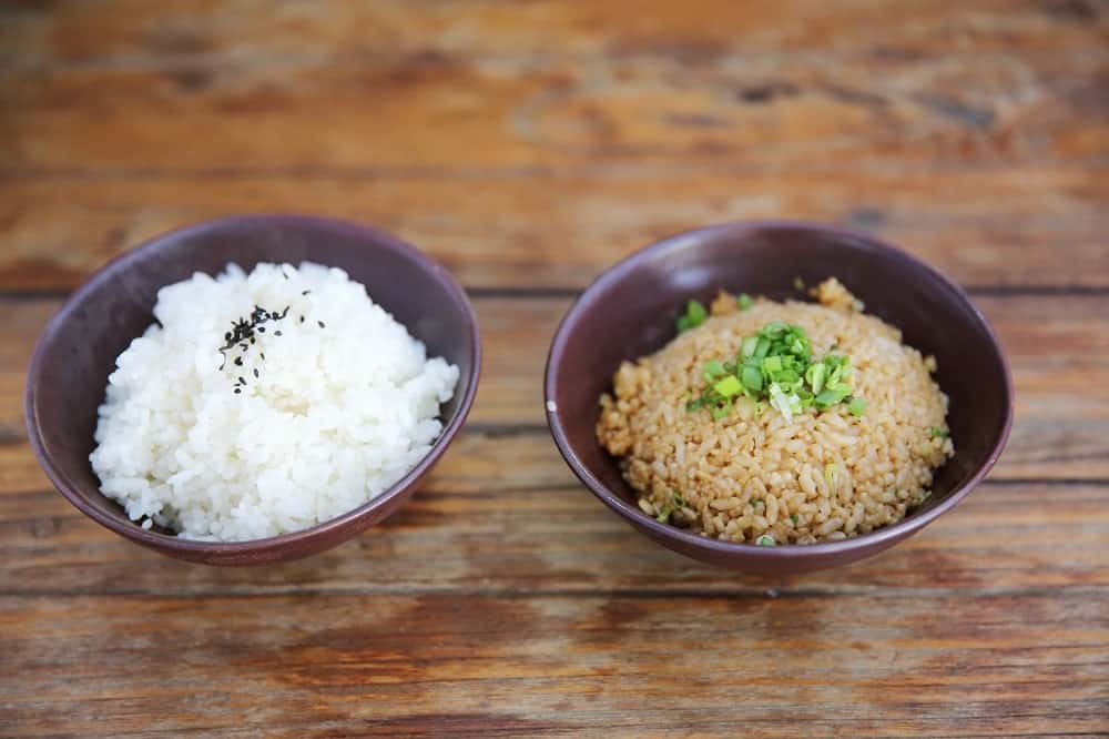 This is a bowl of steamed rice and a bowl of fried rice on a wooden table.
