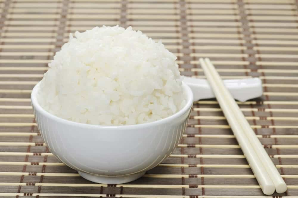 This is a bowl of steamed rice on a bamboo mat with a pair of chopsticks.