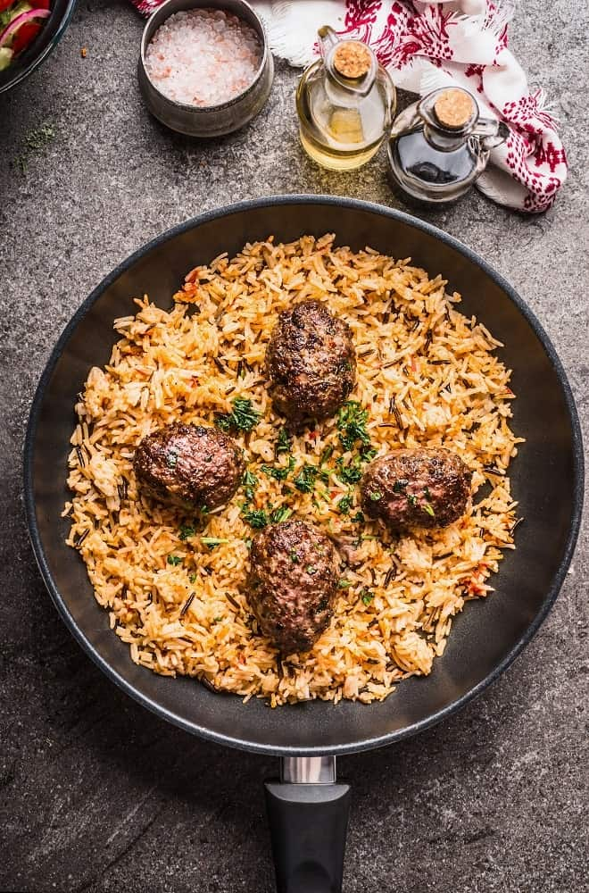 This is a freshly-cooked fried rice with meatballs on a frying pan.