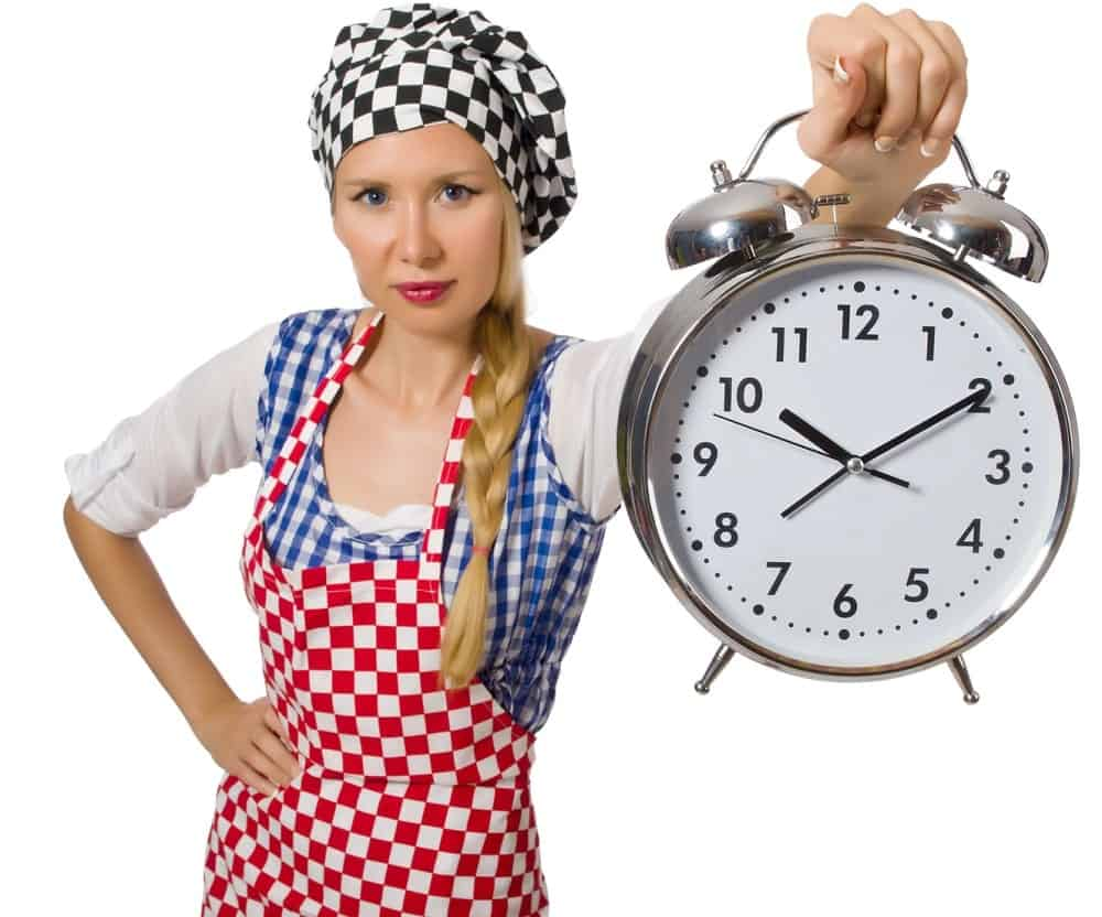 A home cook holding a clock to set the time.