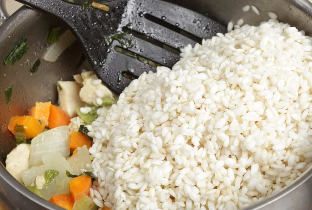 Arborio rice to a bowl of frying chicken, onion, carrot and celery