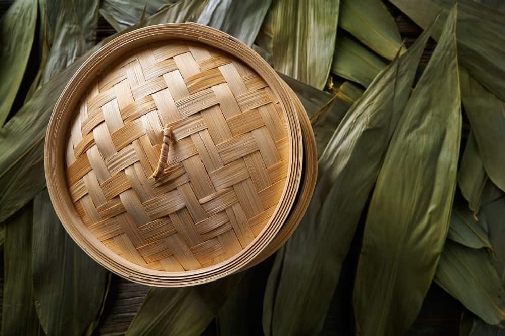 A covered bamboo steamer surrounded by wheat leaves.