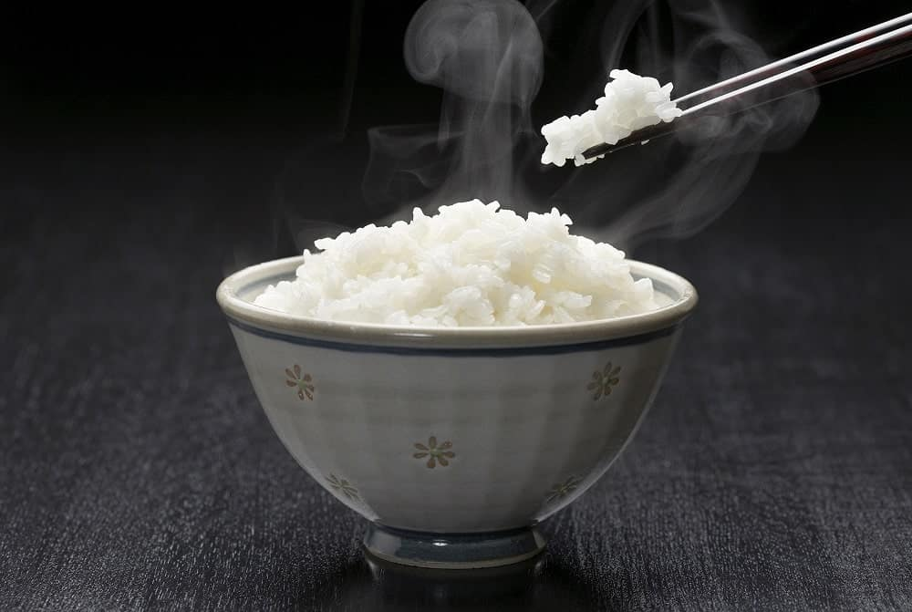 A small bowl of warm white rice with chopsticks.