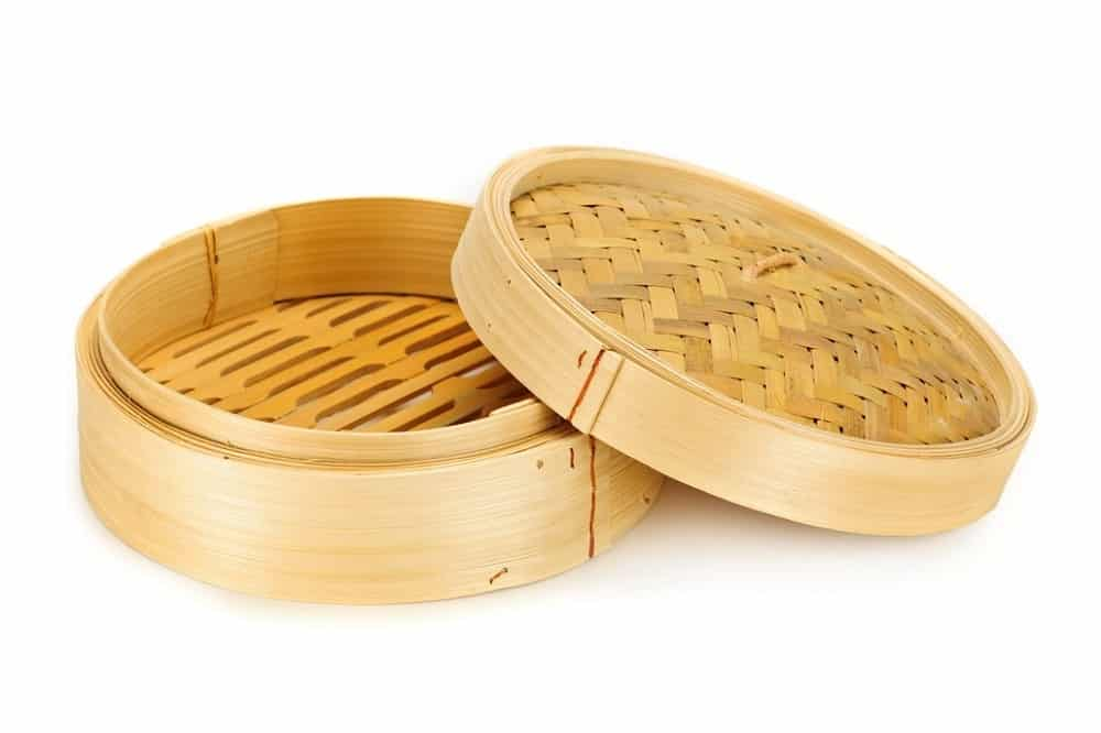 An empty bamboo steamer in a white background.