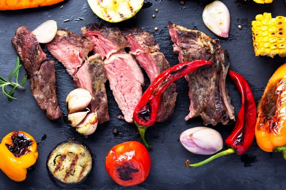 A perfectly grilled steak on a metal pan, along with some grilled tomatoes, bell peppers, onions, and corn on the side.