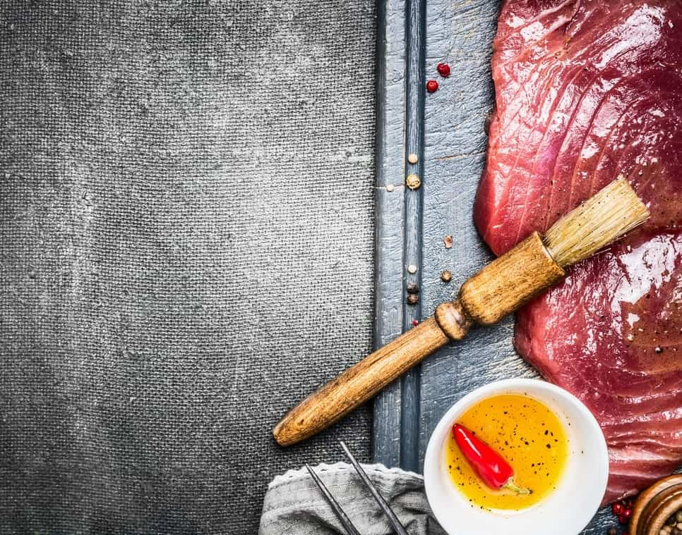 Raw meat on a metal pan, with some spicy seed oil and a basting brush on the side.