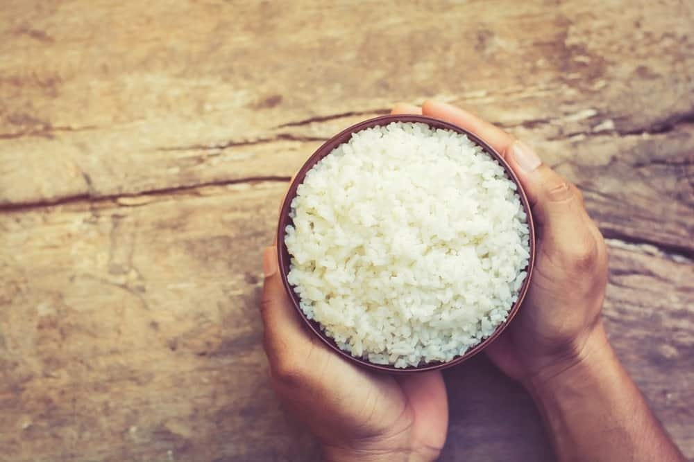 This is a bowl of old rice on a wooden table held with two hands.