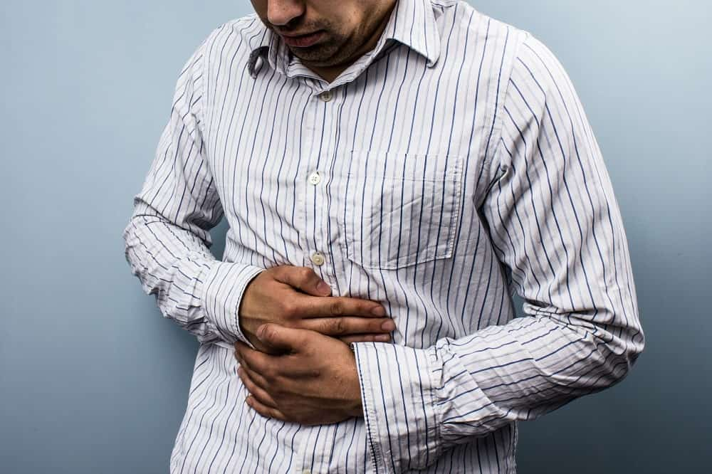 This is a man clutching his abdomen in pain.