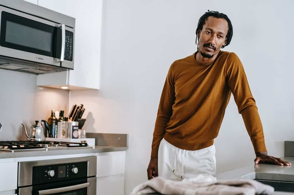 A black man wearing a brown sweater while standing in kitchen and thinking.