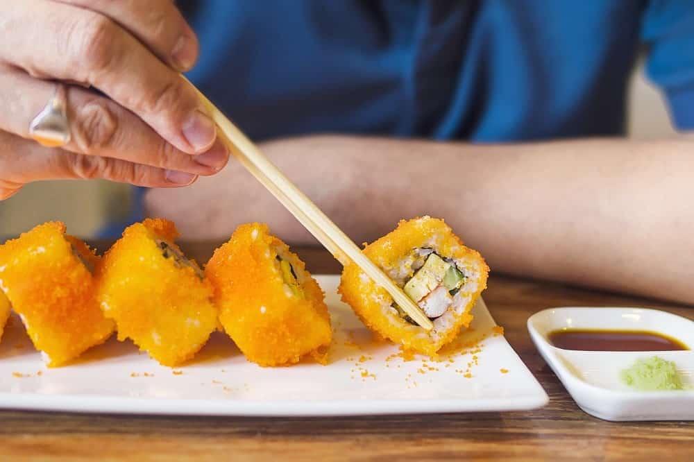 Man eating sushi rice with chopsticks.