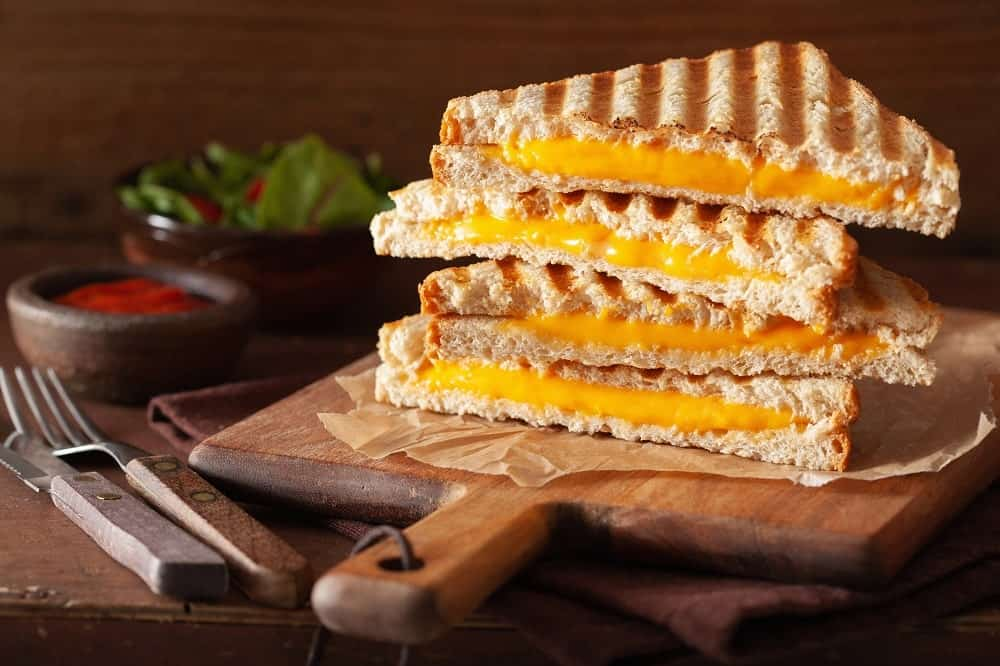 Cheese toastie sandwiches on a wooden board.