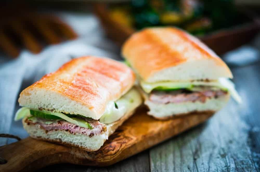 This is a Cubano Sandwich on a wooden board.