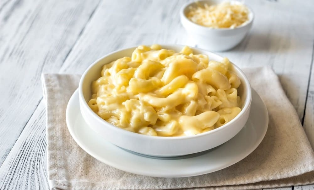 Portion of mac and cheese in white bowls.