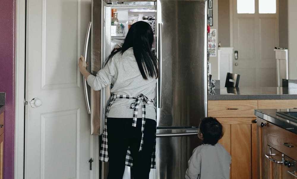 Mother is opening the fridge together with her child standing in front.